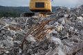 Mountain of debris with yellow excavator in the background Royalty Free Stock Image