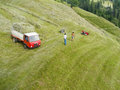 Mountain farmers with tractor schenna italien july high angle view on a steep alpine meadow and two field workers at work Stock Photo