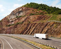 Mountain highway a large white trailer truck drives through a pass with steep sedimentary rock to the sides of the road Stock Images
