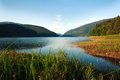 Mountain lake in green forest on blue sky background