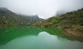 Mountain lake tranquil with green water and reflection at overcast weather with fog arpat crimea Royalty Free Stock Photo