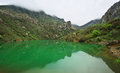 Mountain lake tranquil with green water and reflection at overcast weather with fog arpat crimea Stock Images