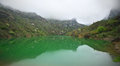 Mountain lake tranquil with green water and reflection at overcast weather with fog arpat crimea Royalty Free Stock Images