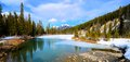 Mountain landscape panorama of a tranquil lake in the canadian rockies during early spring Royalty Free Stock Photo