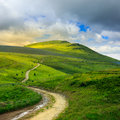 Mountain path uphill to the sky summer landscape through field turns Royalty Free Stock Image