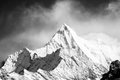 Mountain peak in monotone with snow cover there is clouds background Stock Photo