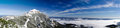 Mountain peak over a sea of clouds in winter panoramic picture composed from stitched images Royalty Free Stock Image