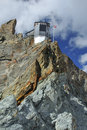 Mountain refuge perched on rock spine Stock Photos