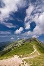 Horský hřeben a modrá obloha s mraky