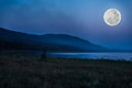 Mountain and river against blue sky and beautiful full moon at n Royalty Free Stock Photo