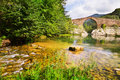 Mountain river with medieval arched bridge in  Pyrenees Royalty Free Stock Photo
