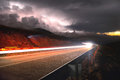 The mountain road with the car passing by the sunset on the right and a thunderstorm with lightning left is shot on a Royalty Free Stock Photo