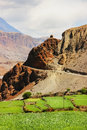 Mountain road and green fields in a mountain gorge. Nepal. The Himalayan mountains. Kingdom of `Lower Mustang`. Trekking in the vi Royalty Free Stock Photo