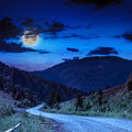 Mountain road near the coniferous forest with cloudy moon sky Royalty Free Stock Photo