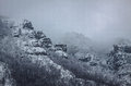 A mountain rock covered with snow fresh and grey sky and fog Stock Images