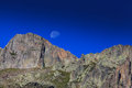 Mountain scenery in the french alps in summer with rocky cliffs blue sky and moonrise Stock Photo
