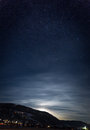 Mountain silhouette against starry nigh sky and shining moon Royalty Free Stock Photo