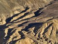 Mountain slope of yellow color, broken by longitudinal cracks of ravines, the Himalayas, Northern India.