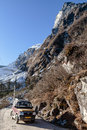 Mountain with snow and leaves less trees. Below with dirt road and four wheel drive tourist car on the way to Zero Point Royalty Free Stock Photo
