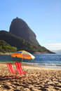 Mountain Sugarloaf sun umbrella and chairs on red beach (Praia Royalty Free Stock Photo