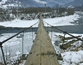 Mountain suspension bridge across river Royalty Free Stock Images