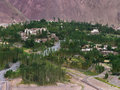 The mountain village of Alchi in the Ladakh valley: white houses and temples on the hills, green trees and fields, the river bed o Royalty Free Stock Photo