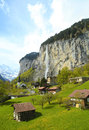 Mountain village with church and waterfall alps switzerland beautiful traditional in the vertical image Stock Photos