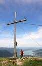 Mountaineer and mountain cross beautiful view over lake tegerns standing beside tegernsee bavaria germany Stock Photos