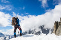 Mountaineer reaches the top of a snowy mountain Stock Images
