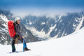Mountaineer reaches the top of a snowy mountain in sunny day Royalty Free Stock Photos