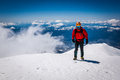 Mountaineer on snowy mountain top. Royalty Free Stock Photo