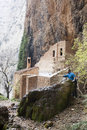Mountaineer wetting his hand in a waterfall in front of an hermitage huesca spain Stock Photos