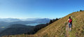 Mountaineering woman view over bavarian alp back walking towards the summit cross beautiful panoramic alps and lake Royalty Free Stock Photos