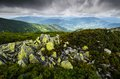 Mountains with mossy rocks in the bushes on the mountain landscape heavy low clouds and distant Stock Photo