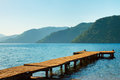 Mountains and old wooden pier to the sea Stock Photo