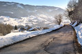 Mounting road along a village in winter Stock Photo