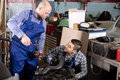 Mounting specialists in coveralls working cheerful at auto repair shop Royalty Free Stock Photo