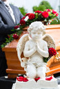 Mourning man at funeral with coffin on red rose standing casket or Royalty Free Stock Photography