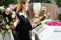Mourning people at funeral with coffin men and women on pink rose standing casket or Royalty Free Stock Photo