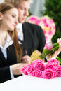 Mourning people at funeral with coffin men and women on pink rose standing casket or Stock Photo