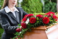 Mourning woman at funeral with coffin on red rose standing casket or Stock Photo