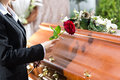 Mourning woman at funeral with coffin on red rose standing casket or Royalty Free Stock Image
