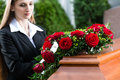Mourning woman at funeral with coffin on red rose standing casket or Stock Image