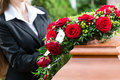 Mourning woman at funeral with coffin on red rose standing casket or Royalty Free Stock Photography