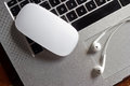 Mouse and earphone on laptop computer keyboard