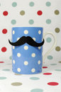 Moustache on a blue coffee mug morning mustache against polka dot background for fathers day or movember to raise awareness for Stock Photos