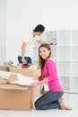 Move in vertical image of a smiling girl packing things on the foreground Stock Image