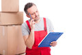 Mover guy making thinking gesture and holding clipboard Royalty Free Stock Photo