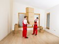 Movers in new house with lot of boxes Stock Photography