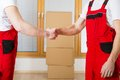 Movers in new house with lot of boxes behind them Royalty Free Stock Photos